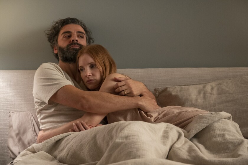 A man and a woman embrace in a bed.