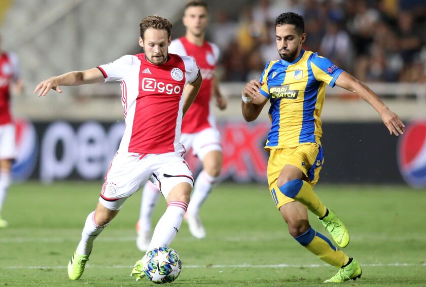 Ajax's defender defender Daley Blind (L) vies for the ball with APOEL's midfielder Musa Suliman during the UEFA Champions League playoff football match between Cyprus' APOEL Nicosia and Netherland's Ajax Amsterdam at the GSP stadium in Nicosia on August 20, 2019. (Photo by - / AFP)-/AFP/Getty Images ** OUTS - ELSENT, FPG, CM - OUTS * NM, PH, VA if sourced by CT, LA or MoD **