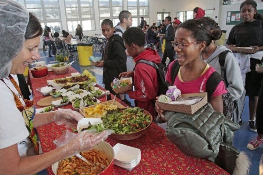 Volunteer Renee Meshul serves Randee Mervin from the garden table at lunch at Mark Twain Middle School in Venice.