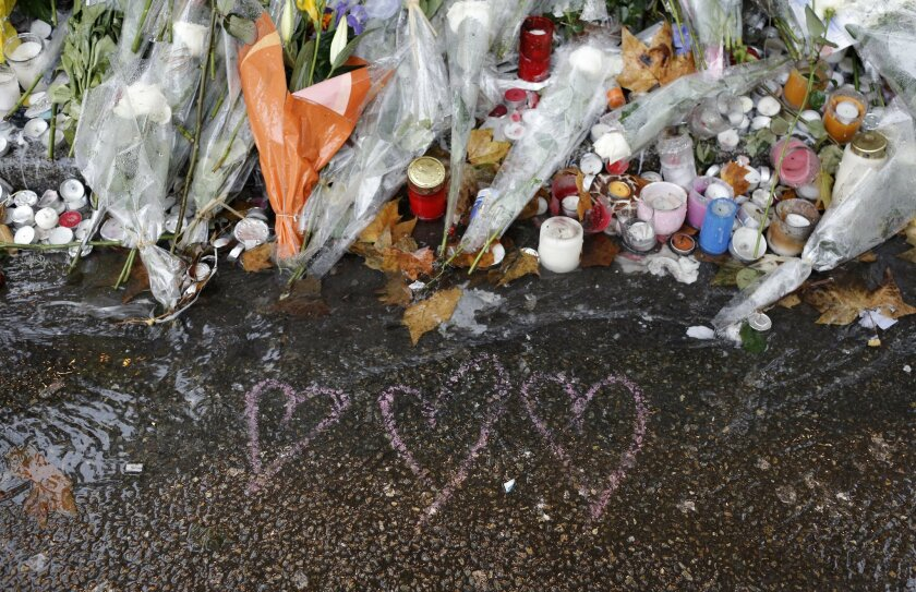 Hearts drawn and flowers lay on the pavement at a bar where an attack took place last week, Friday on, Friday, Nov. 20, 2015 in Paris. old rain extinguished the flickering candles and drenched the packets of flowers outside the Paris attacks sites Friday, but people came anyway — to pay tribute, to mourn, to reflect on their city's losses one week later. (AP Photo/Laurent Cipriani)
