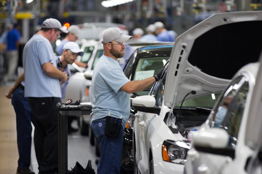 FILE - In this July 31, 2012, file photo, employees work on vehciles at the Volkswagen plant in Chattanooga, Tenn. Volkswagen on Thursday, Oct. 29, 2015 said it is sticking with planned investments at its Chattanooga plant — including production of a new SUV there next year — despite the uncertaint
