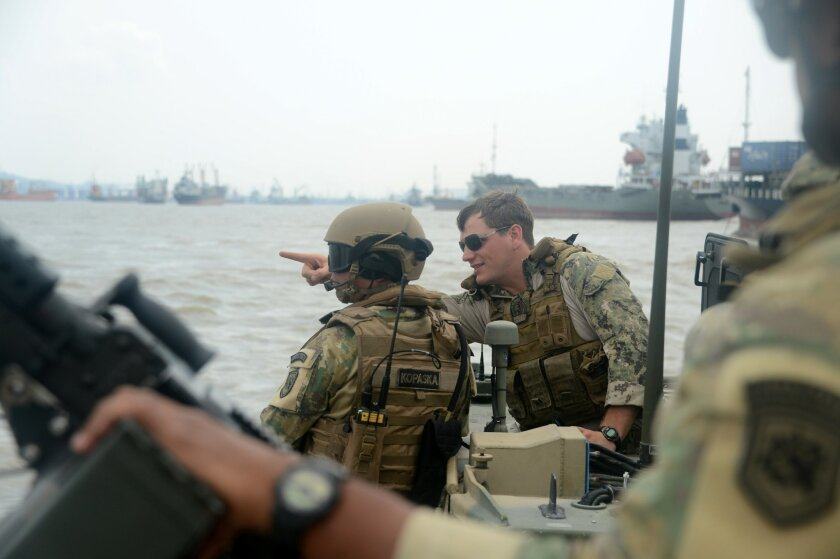 """SURABAYA, Indonesia (Aug. 6, 2015)  Lt. David Nartker, right, assigned to Coastal Riverine Squadron (CRS) 3, talks with an Indonesian """"Kopaska"""" Naval Special Forces member while practicing small boat tactics and maneuvers during Cooperation Afloat Readiness and Training (CARAT) Indonesia 2015."""