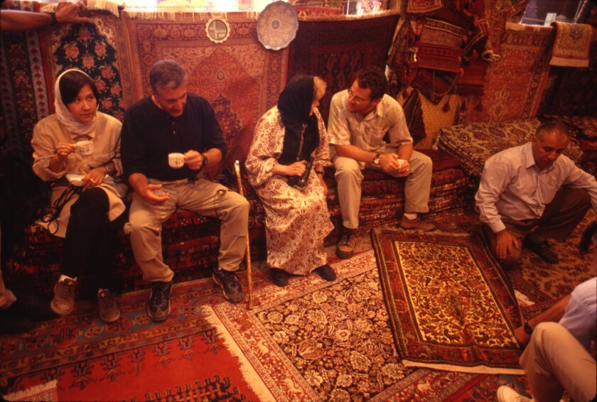 At a carpet vendor's shop in Isfahan, we took tea. At right, you can see the salesman talking. Iran, 1998.