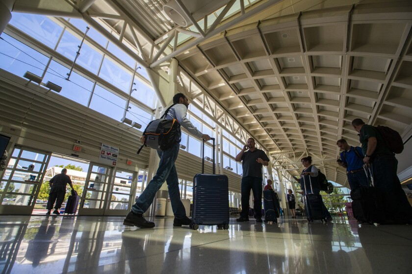 People walk through Ontario International Airport in August 2019.