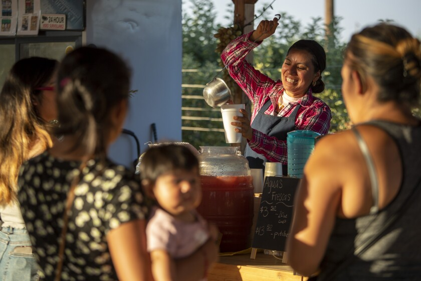 Farmer Liset Garcia pours a cup of aguas frescas at her Sweet Girl Farms stand on Thursday, July 1, 2021 in Reedley, CA.