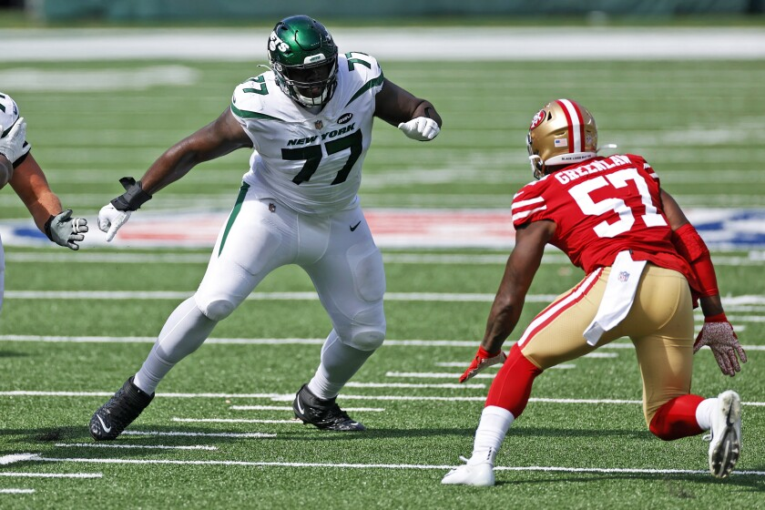 FILE - In this Sunday, Sept. 20, 2020, file photo, New York Jets offensive tackle Mekhi Becton (77) looks to block against the San Francisco 49ers during an NFL football game in East Rutherford, N.J. Becton flings 300-pound defenders to the ground as if they're merely little rag dolls. This is exactly what the Jets envisioned when they drafted the 6-foot-7, 363-pound behemoth out of Louisville. (AP Photo/Adam Hunger, File)