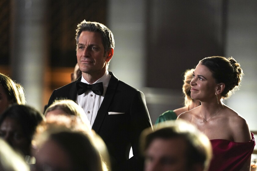 A woman in an evening gown smiles up at a man in a tuxedo