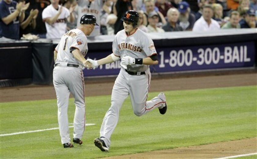 San Francisco Giants first baseman Brett Pill is greeted by San Francisco Giants third base coach Tim Flannery as he rounds third base after hitting a two-run home run against the San Diego Padres in the second inning during their baseball game Tuesday, Sept. 6, 2011, in San Diego. The hit was Pill's first major league home run. (AP Photo/Gregory Bull)