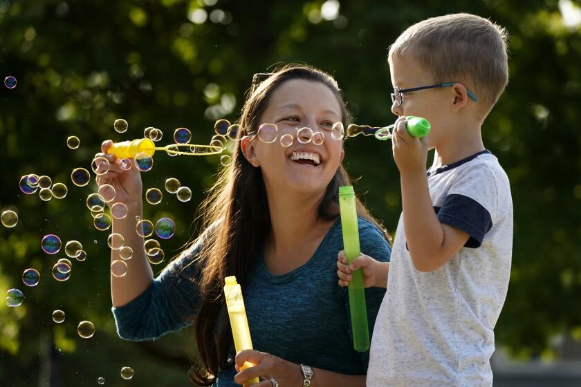 Claire Reagan juega con su hijo Evan, de 5 años, afuera de su casa en Olathe, Kansas, el lunes 21 de septiembre de 2020. (AP Foto/Charlie Riedel)