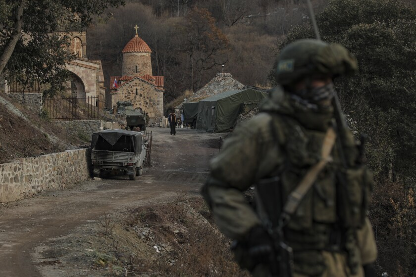 A man in full military gear, carrying a rifle, stands near a monastery. In the background are military vehicles and tents.