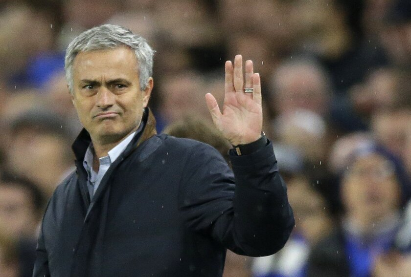 Chelsea manager Jose Mourinho waves to fans singing in his support during the Champions League Group G soccer match between Chelsea and Dynamo Kiev at Stamford Bridge Stadium in London,  Wednesday, Nov. 4, 2015. (AP Photo/Matt Dunham)