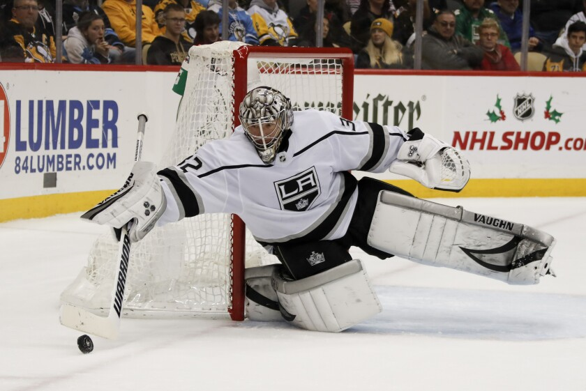 Kings goalie Jonathan Quick clears the puck away from the net against the Penguins on Dec. 14, 2019.