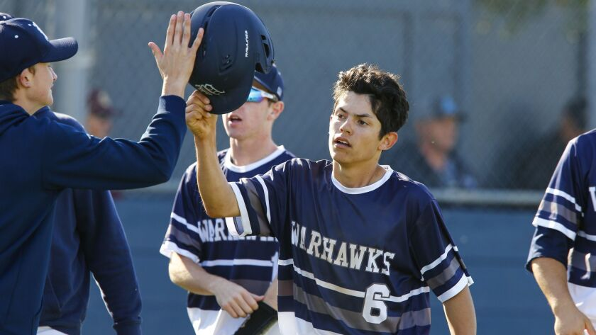 Madison right fielder Adam Lovato high fives teammates after scoring in the fifth inning against La Costa Canyon.