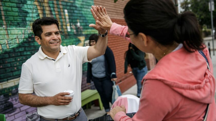 Congressman-elect Jimmy Gomez gets a high-five from former primary opponent Vanessa Aramayo the day after winning the election to represent the 34th Congressional District.