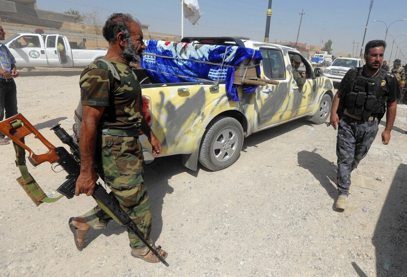 The coffin of an Iraqi Shiite militia fighter is transported on the outskirts of Amerli. Over the weekend, U.S. airstrikes on Islamic State strongholds and a ground offensive by Iraqi toops, including Kurds, helped break a siege of the town.