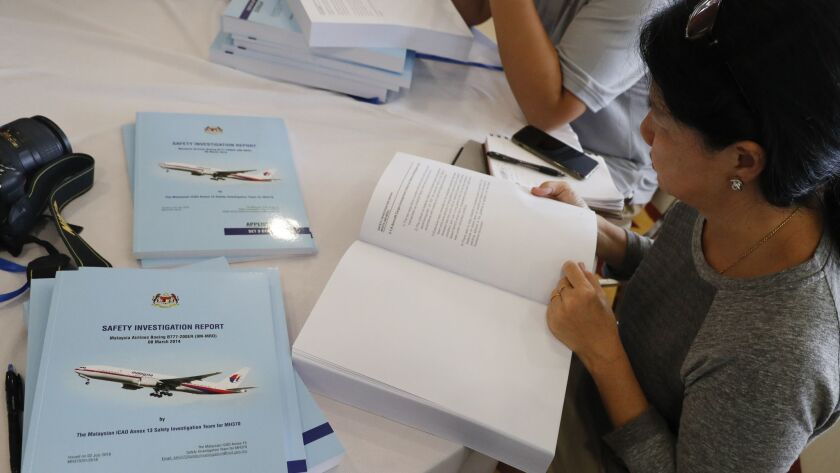 Copies of the final investigation report on missing flight MH370 are offered to the media in Putrajaya on Monday.