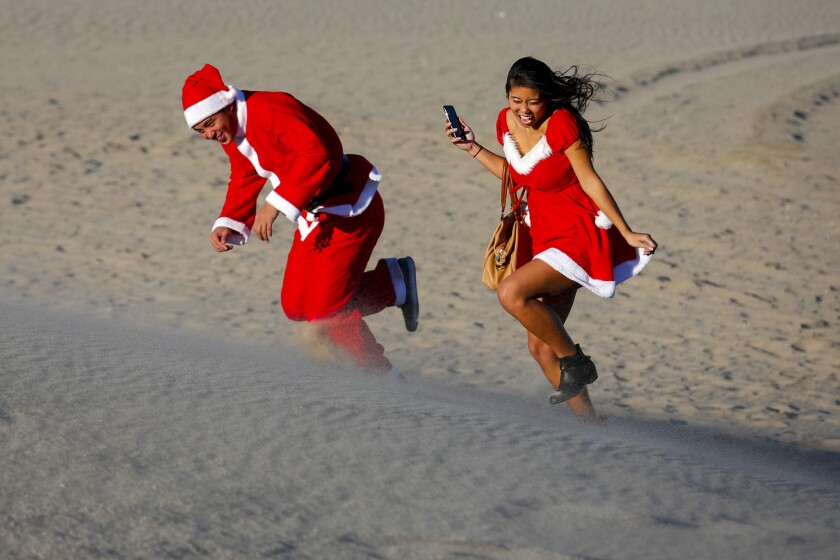 Lawrence Tran and Erika Yagui of Torrance braved the wind in Hermosa Beach on Christmas Day. High winds are expected in L.A. and Ventura counties on Monday.