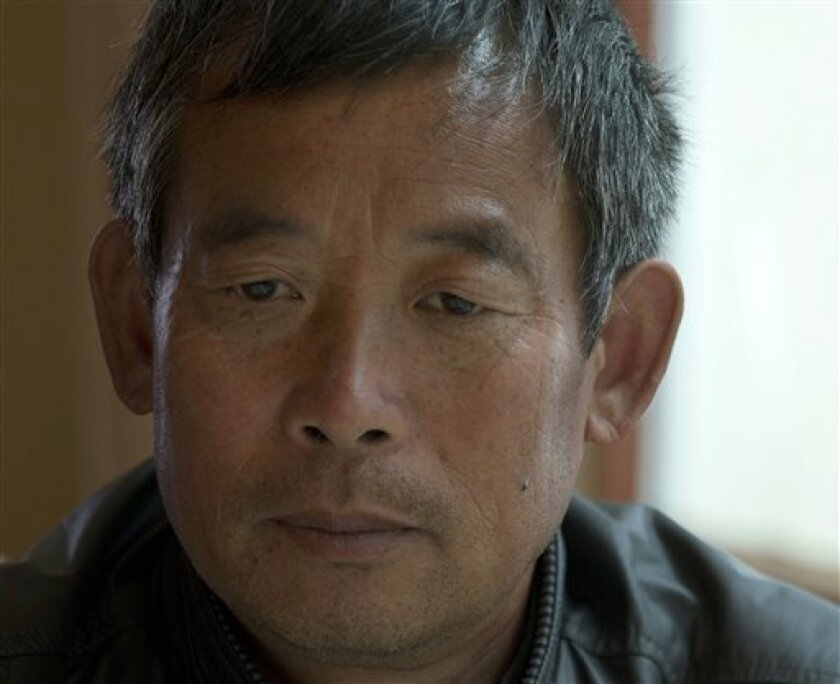 FILE - In this Wednesday, April 10, 2013 file photo, Chen Guangfu sits at a restaurant in Beijing. Chen, the oldest brother of Chinese activist Chen Guangcheng who fled house arrest and later settled in the U.S., said he was beaten up Thursday, May 9, 2013 by unidentified men, part of an uptick in harassment possibly linked to the activist's plans to visit Taiwan. Chen Guangfu said he was followed by a black car without a license plate while he was on a motor-scooter visiting a relative in anoth