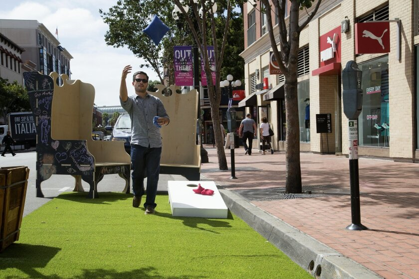 Greg Parkington plays a game of corn hole on a Fifth Avenue parking space, reconfigured as a temporary park for Park(ing) Day.