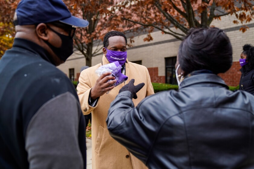 Shannon Rochon, 38, of Detroit hands out masks during a Walk the Vote event at Greater Grace Temple.