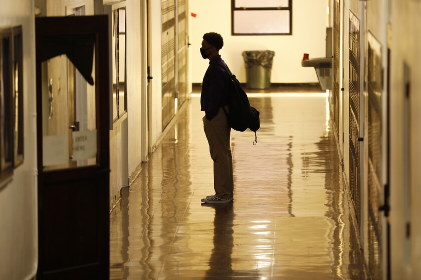 A student stands in a school hallway