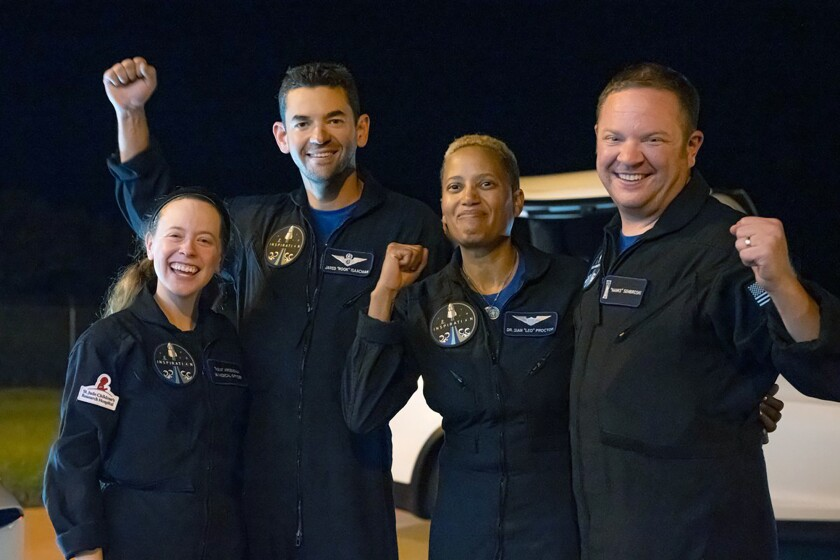 In this image released by Inspiration4, passengers aboard a SpaceX capsule, from left to right, Hayley Arceneaux, Jared Isaacman, Sian Proctor and Chris Sembroski pose after the capsule was recovered following its splashdown in the Atlantic off the Florida coast, Saturday, Sept. 18, 2021. The all-amateur crew was the first to circle the world without a professional astronaut. (Inspiration4 via AP)
