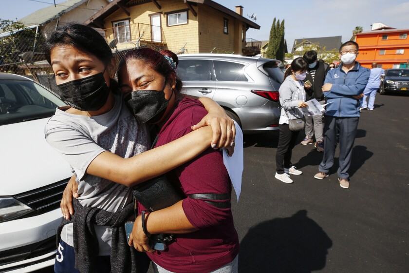 Jeymy Mendoza, 16, hugs her mother, Maria Jimenez, 34, at a mobile COVID-19 vaccine clinic in Los Angeles.