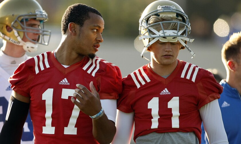 UCLA quarterback Brett Hundley, left, speaks with quarterback Jerry Neuheisel during a spring practice session on April 1. Nueheisel is competing with Asiantii Woulard for the Bruins' backup quarterback role.
