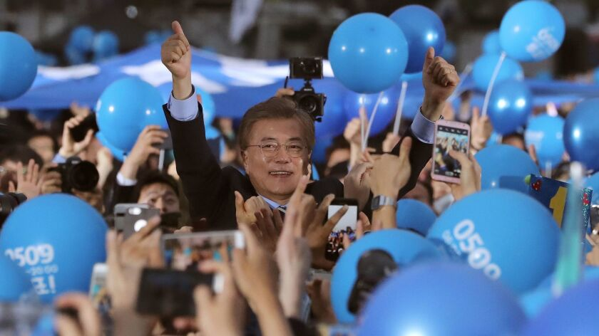 South Korean presidential candidate Moon Jae-in of the Democratic Party gives his supporters a thumb