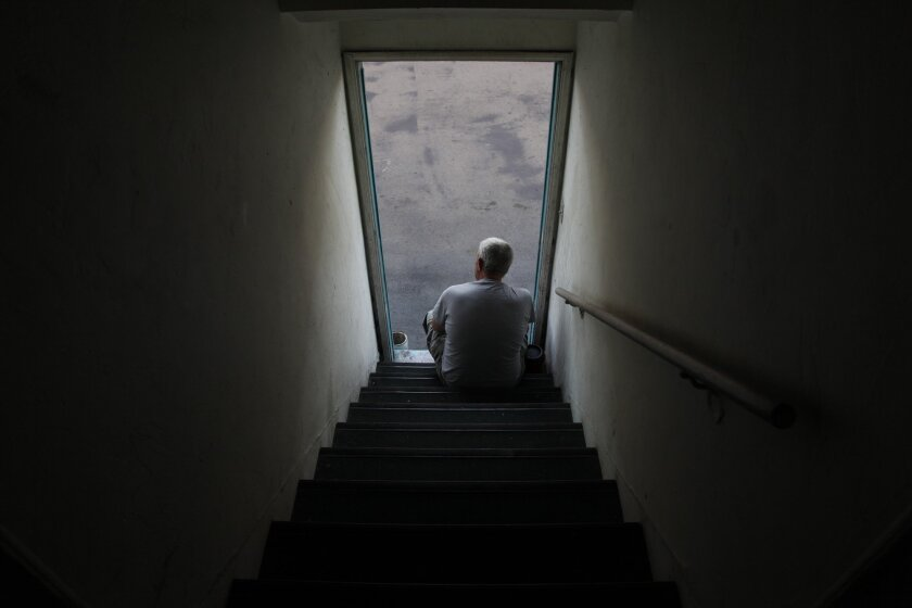 A man sits outside of his La Mesa apartment to escape the heat of his upstairs unit.