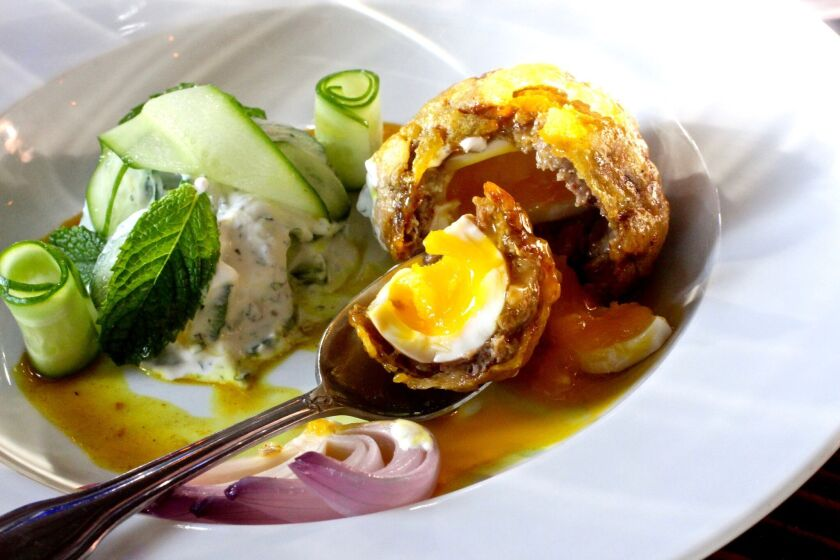 An egg encapsulated with lamb sausage, served with curry jus and a cucumber salad.