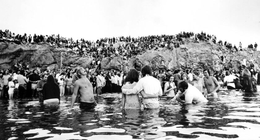 People on a beach watch other people standing, embracing and being baptized in the water.