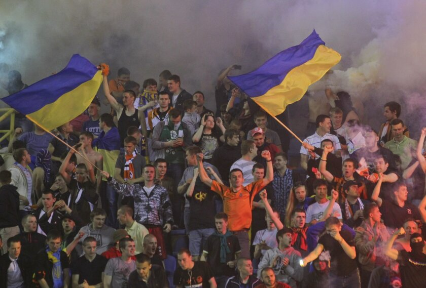 FILE - In this Thursday, May 15, 2014 file photo, Shakhtar's Donetsk supporters wave Ukrainian flags as they react during the final soccer match of Ukraine's Cup between Donetsk's Shakhtar and Dynamo Kiev at Vorskla Stadium in Poltava, Ukraine. Five months after the annexation of Crimea, Russia and Ukraine are now squabbling over soccer clubs in the region. Defying authorities in Ukraine, Russia is incorporating three Crimean teams into its own leagues _ a move that could strain relations between the host country of the 2018 World Cup and the sport's world governing body. Champion Shakhtar Donetsk has been left humbled by the conflict, forced to play its home games in exile in Lviv near the Polish border, a Ukrainian-speaking city that is the cultural opposite of mostly Russian-speaking and industrial Donetsk. (AP Photo/Andrey Lukatsky, File)