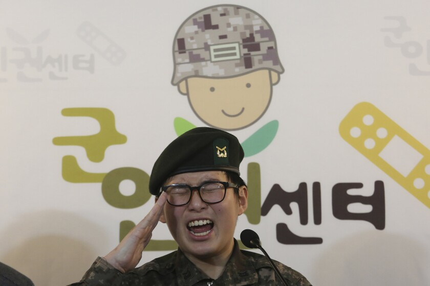 """FILE - In this Jan. 22, 2020 file photo, South Korean army Sergeant Byun Hui-su salutes during a press conference at the Center for Military Human Right Korea in Seoul, South Korea. A South Korean court ruled Thursday, Oct. 7, 2021, that the military unlawfully discriminated against the country's first known transgender soldier by discharging her for undergoing gender reassignment surgery, in a landmark verdict that came seven months after she was found dead at her home. The sign reads """"The Center for Military Human Right Korea."""" (AP Photo/Ahn Young-joon, File)"""