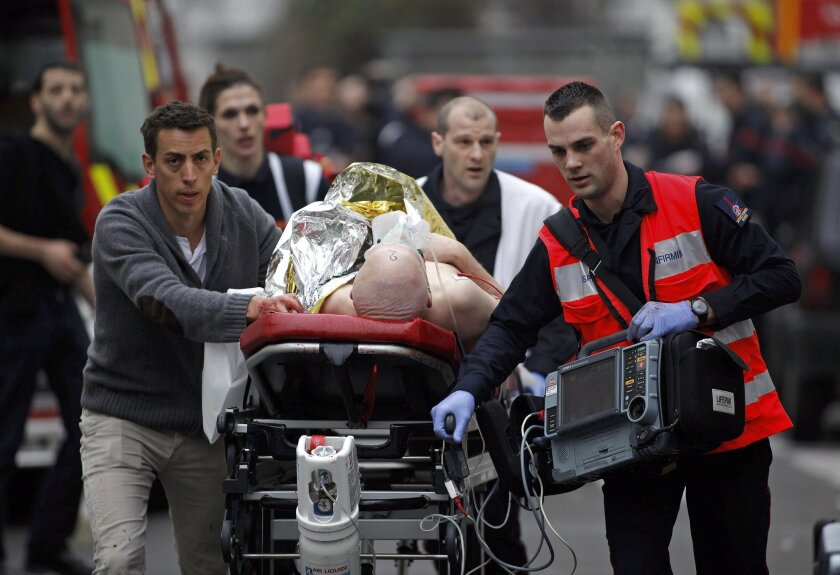 An injured person is evacuated outside the French satirical newspaper Charlie Hebdo's office, in Paris on Jan. 7, 2015.