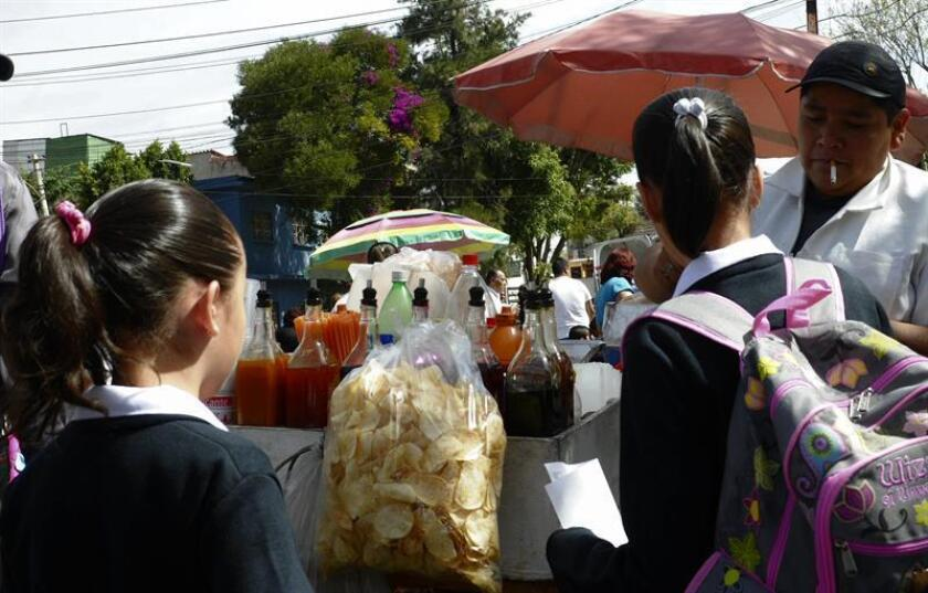 Unas niñas estudiantes compran frituras afuera de un colegio en la capital mexicana. EFE/Archivo