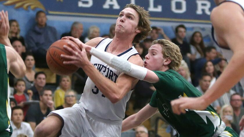 Newport Harbor's Dayne Chalmers drives the basket for a lay-up as Edison's Justin Strauss tries to s