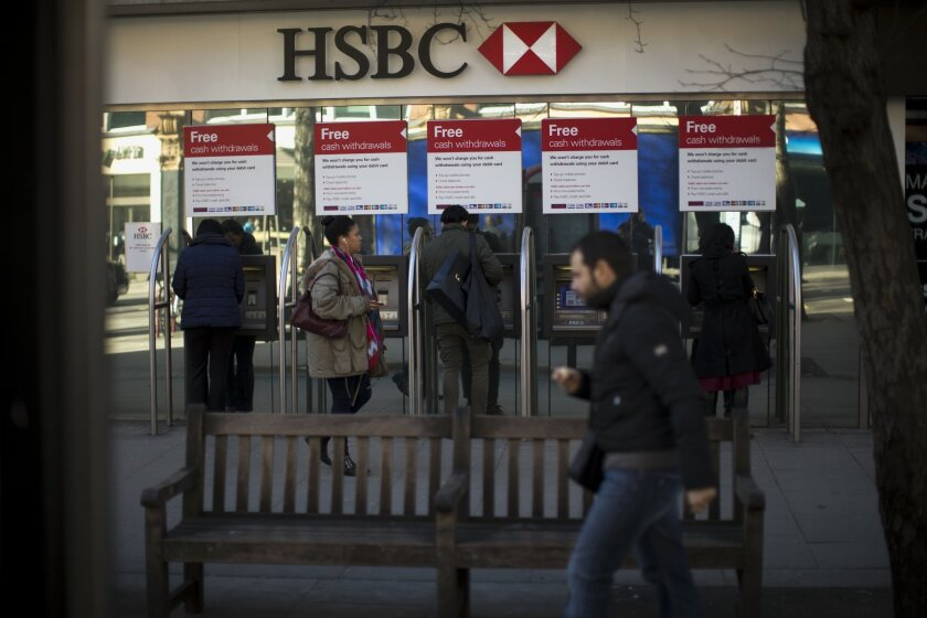 """FILE - This is a Wednesday, Feb. 18, 2015 file photo of people as they use ATM machines outside a branch of HSBC in London. HSBC executives offered a fresh mea culpa Monday Feb. 23, 2015 as its chief executive found himself personally mired in the scandal surrounding allegations that the bank helped wealthy clients dodge taxes. Europe's biggest bank by market value said past practices at its Swiss private bank were """"unacceptable"""" as it posted 2014 net income that fell 16 percent to $13.7 billion. Meanwhile, Britain's Guardian newspaper reported that Chief Executive Officer Stuart Gulliver had an account at the same unit. (AP Photo/Matt Dunham)"""