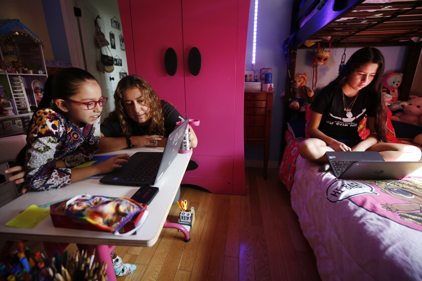 Students study with laptops at home as mom assists