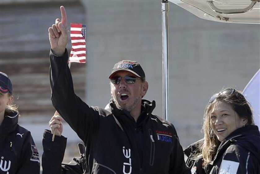 FILE - In this Tuesday, Sept. 24, 2013, file photo, Oracle CEO Larry Ellison, center right, gestures after Oracle Team USA won the 18th race of the America's Cup sailing event against Emirates Team New Zealand, in San Francisco. Oracle is trying to ward off a shareholder rebellion against policies that have consistently made its billionaire co-founder, Larry Ellison, one of the best-paid CEOs in the world. (AP Photo/Ben Margot, File)