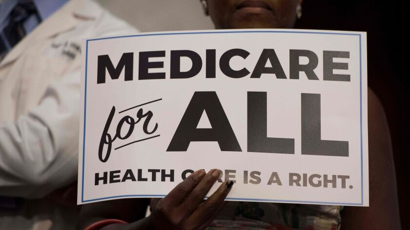 In this file photo, a member of the audience holds up a placard as U.S. Sen. Bernie Sanders discusses Medicare for All legislation in Washington, DC. Below, a biopharmacist from Carmel Valley outlines how universal healthcare could help communities of color.