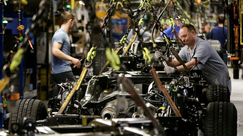 FILE - In this March 13, 2015, file photo, a worker prepares a chassis to receive an engine on a new