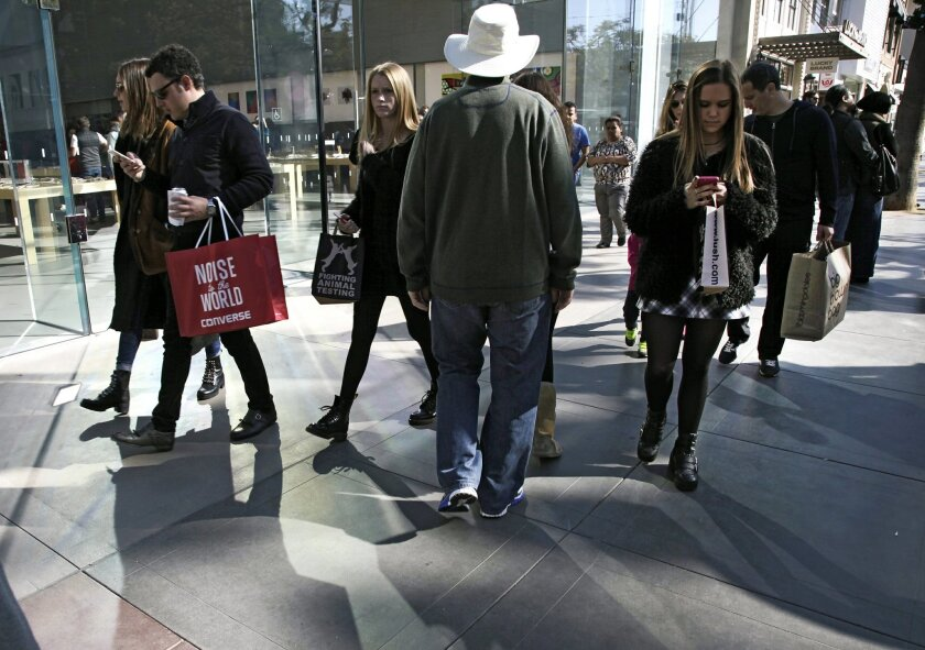 In this Saturday, Jan. 3, 2015 photo, shoppers walk along the retail, dining and entertainment area of the Third Street Promenade in Santa Monica, Calif. The University of Michigan issues its monthly index of consumer sentiment for February on Friday, Feb. 27, 2015. (AP Photo/Richard Vogel)