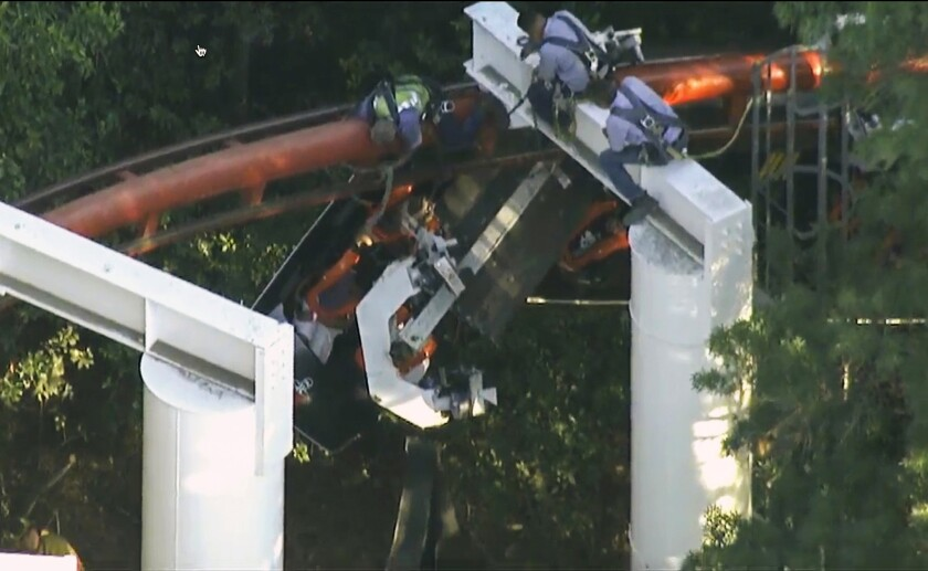 In this frame grab from video provided by KTLA-TV Channel 5, workers at Six Flags Magic Mountain rescue people trapped on the Ninja roller coaster after it partially derailed this week.