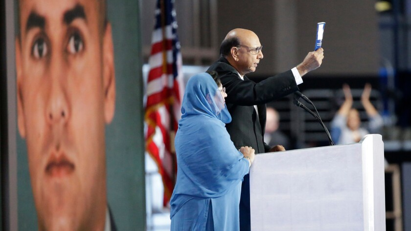 Khizr Khan, whose son Humayun Khan was killed while serving in Iraq, speaks at the Democratic National Convention next to his wife Ghazala Khan and a large photo of their son.