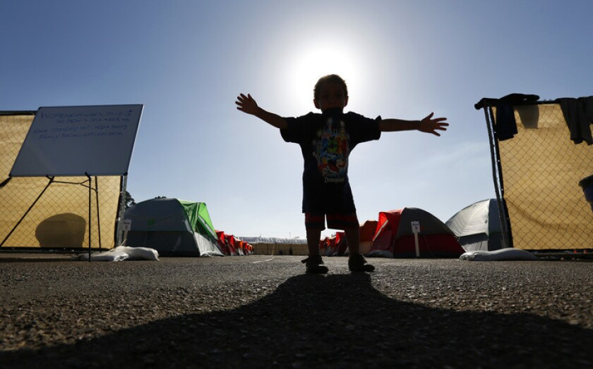In this file photo, a child stands at the entrance to a city-sanctioned homeless camp near Balboa Park. Below, a writer says people experiencing homelessness need somewhere to go, now more than ever.