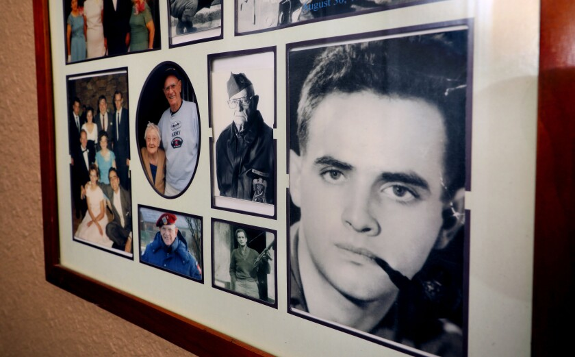 """Photos of World War II veteran Richard """"Dick"""" Field are displayed with various family photos in the home of his daughter Ginni Field. Close at right is Field during WWII and just to the left is him later in life. He passed away in 2016 at age 91."""