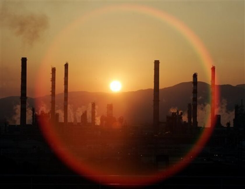 FILE - In this Tuesday, May 2, 2006, file photo, the sun sets over a oil refinery in Tarragona, Spain. In the 2000s, large investors in so-called clean technology wanted to finance companies that would help eliminate the world's dependence on oil, natural gas and coal. But in 2013, clean technology investment funds are not trying to replace the fossil fuel industry, they're trying to help it by financing companies that can make mining and drilling less dirty.( AP Photo/Manu Fernandez)