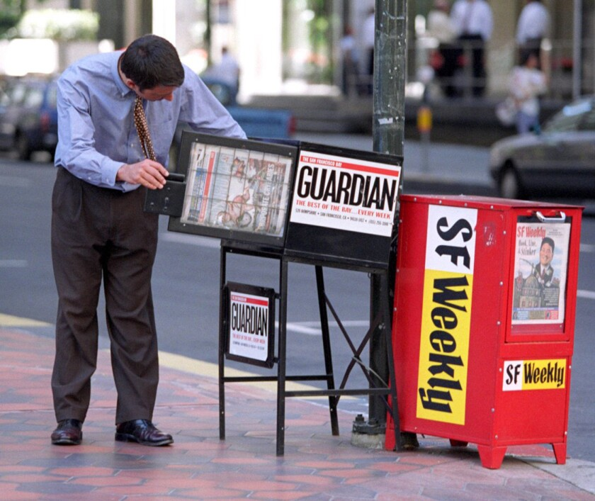 A man picks up a weekly San Francisco Bay Guardian at the corner of Sacramento and Davis streets in San Francisco.