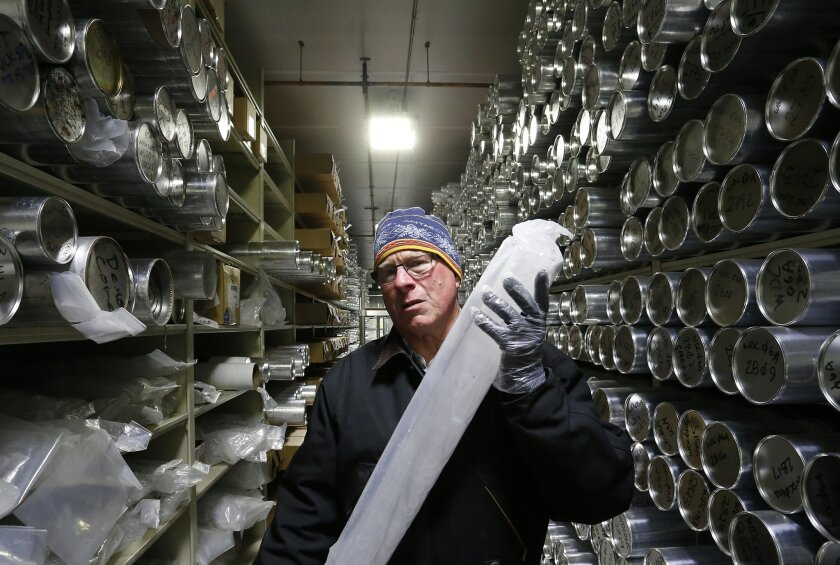 In this Aug. 8, 2016 photo, Geoffrey Hargreaves, curator of the National Ice Core Laboratory, carries an arctic ice core inside the minus-33 degree Fahrenheit environment of the lab's archive warehouse, in Lakewood, Colo. Using a wide range of data, from ice cores to trace gas analysis and other me